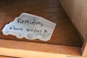 note on wooden shelf that camper tv remotes are in the house for the winter