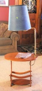 scuffed up wooden end table and attatched lamp with blue broken shade