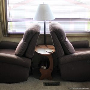Wooden endtable nestled tightly between two recliners